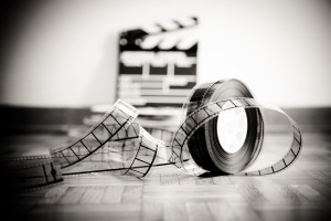 35 mm cinema film reel and out of focus movie clapper board in background on wooden floor in vintage black and white